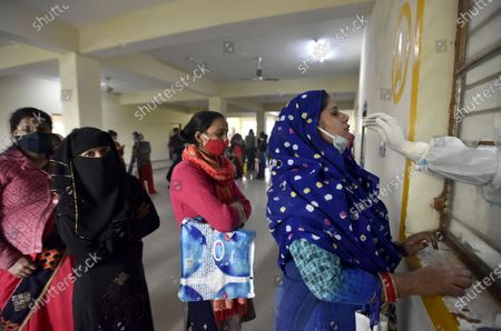 A health worker collects sample for COVID-19 test, at Swami Daya Nand Hospital, Dilshad Garden, on December 3, 2020 in New Delhi, India.