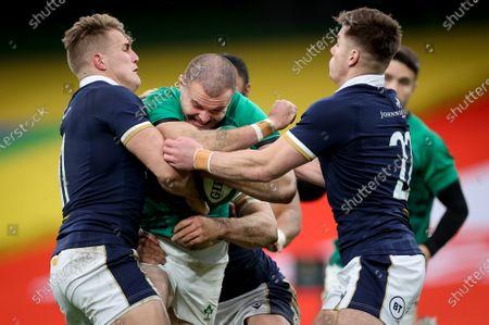 Ireland vs Scotland. Ireland's Jacob Stockdale is tackled by Duhan Van der Merwe and Huw Jones of Scotland