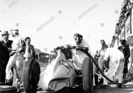 Monza, Italy. 11 September 1938. Rudolf Caracciola talks to Max Sailer (out of car, left) as Manfred von Brauchitsch takes over the Mercedes-Benz W154, 3rd position, pitstop, action, refuelling. World Copyright: Robert Fellowes/LAT Photographic Ref: 38ITA02