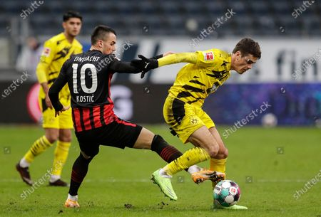 Frankfurt's Filip Kostic, left, and Dortmund's Giovanni Reyna challenge for the ball during a German Bundesliga soccer match between Eintracht Frankfurt and Borussia Dortmund in Frankfurt, Germany