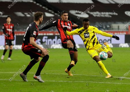 Dortmund's Youssoufa Moukoko, right, shoots against Frankfurt's David Abraham, left, during a German Bundesliga soccer match between Eintracht Frankfurt and Borussia Dortmund in Frankfurt, Germany