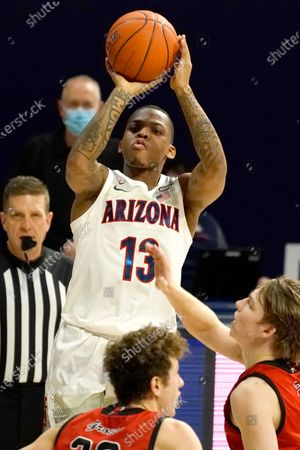 Stock Picture of Arizona guard James Akinjo (13) shoots over Eastern Washington guard Jacob Groves (33) and Jack Perry (11) during the first half of an NCAA college basketball game, in Tucson, Ariz