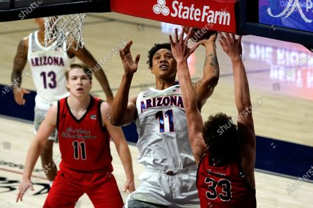 Stock Photo of Arizona forward Ira Lee (11) shoots between Eastern Washington guard Jack Perry (11) and Jacob Groves (33) during the first half of an NCAA college basketball game, in Tucson, Ariz