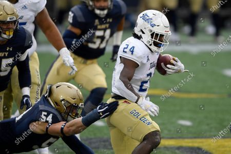 Tulsa running back Corey Taylor II (24) runs with the ball past Navy linebacker Diego Fagot (54) during the first half of an NCAA college football game, in Annapolis, Md