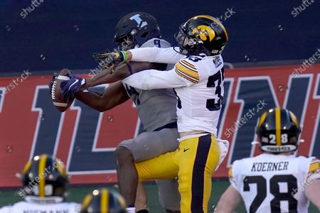 Stock Photo of Illinois wide receiver Josh Imatorbhebhe (9) catches a touchdown pass as Iowa defensive back Riley Moss defends during the first half of an NCAA college football game, in Champaign, Ill