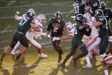 Michigan State's Julian Barnett, center, returns a kick against Ohio State's Cody Simon, left, Teradja Mitchell, right, and Cade Stover as Michigan State's Jeff Pietrowski (47), David Kruse (49) and Terry O'Connor (58) block during an NCAA college football game, in East Lansing, Mich. Ohio State won 52-12