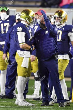 Notre Dame quarterback Ian Book (12) is greeted by coach Brian Kelly after coming out of the game during the fourth quarter of the team's NCAA college football game against Syracuse, in South Bend, Ind