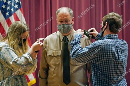 """John Forrest Kelly, right, and his sister Morgan Kelly, children of Rep. John """"Trent"""" Kelly, R-Miss., center, adjust a set of major general shoulder boards on his shirt, during his promotion ceremony at the Mississippi Army National Guard headquarters, in Jackson, Miss. The congressman will also assume the position of Assistant Adjutant General in the Mississippi Army National Guard along with his promotion"""