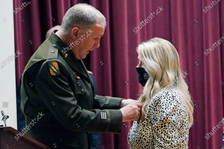 """Moments before being promoted, Brig. Gen. John """"Trent"""" Kelly, of the Mississippi Army National Guard, attaches a set of general stars to the dress of his wife Shelia Kelly, noting that she is his """"Household 6"""" during his promotion ceremony to major general at state headquarters, in Jackson, Miss. Kelly, who is also the Republican congressman for Mississippi's First Congressional District, will also assume the position of Assistant Adjutant General in the Mississippi Army National Guard along with his promotion. The term, """"Household 6"""" is used by the military to denote the spouse who runs things at home not only everyday but also while their military spouse is away during deployments, TDYs, and training"""