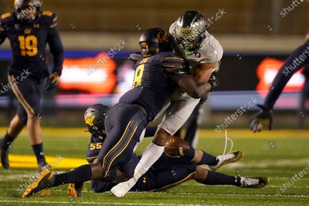 Oregon wide receiver Johnny Johnson III, center right, fumbles the ball as he is hit by California linebacker Kuony Deng (8) during the second half of an NCAA college football game in Berkeley, Calif., . California recovered the ball