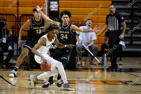 Oklahoma State's Rondell Walker dribbles as Oakland's Jalen Moore guards him during an NCAA college basketball game in Stillwater, Okla