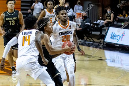 Oakland's Jalen Moore drives past Oklahoma State's Bryce Williams (14) and Keylan Boone (20) in the first half of an NCAA college basketball game in Stillwater, Okla