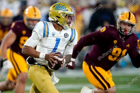 Quarterback Dorian Thompson-Robinson (1) scrambles as Arizona State defensive end Michael Matus (91) pursues during the first half of an NCAA college football game, in Tempe, Ariz