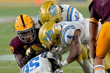 Stock Picture of Arizona State running back Rachaad White, left, is hit by UCLA linebacker Carl Jones (35), defensive back Stephan Blaylock (4) and linebacker Caleb Johnson (40) during the first half of an NCAA college football game, in Tempe, Ariz