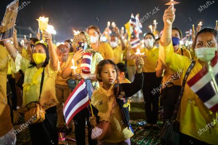 Thai royalist supporters hold candles in front of the Grand Palace at Sanam Luang during a ceremony to celebrate the birthday of late Thai King Bhumibol Adulyadej (Rama 9). Thai King Maha Vajiralongkorn (Rama 10), took part during the ceremony along with other members of the Royal Family.