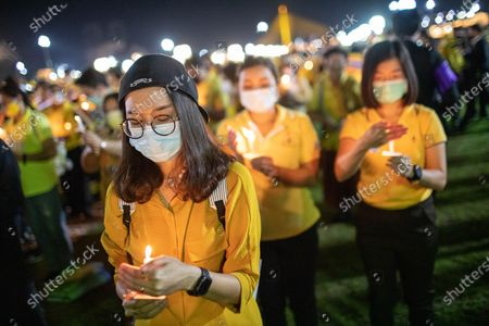 A Thai royalist supporter holds a candle in front of the Grand Palace at Sanam Luang during a ceremony to celebrate the birthday of late Thai King Bhumibol Adulyadej (Rama 9). Thai King Maha Vajiralongkorn (Rama 10), took part during the ceremony along with other members of the Royal Family.