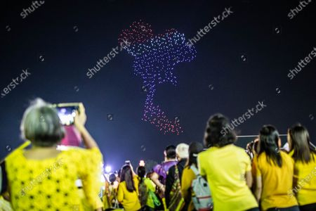 Thai royalist supporters take pictures of a drone lighting performance in front of the Grand Palace at Sanam Luang during a ceremony to celebrate the birthday of late Thai King Bhumibol Adulyadej (Rama 9). Thai King Maha Vajiralongkorn (Rama 10), took part during the ceremony along with other members of the Royal Family.