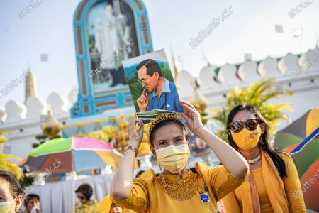 A Thai royalist supporter holds a portrait of late Thai King Bhumibol Adulyadej as she gather in front of the Grand Palace at Sanam Luang during a ceremony to celebrate the birthday of late Thai King Bhumibol Adulyadej (Rama 9). Thai King Maha Vajiralongkorn (Rama 10), took part during the ceremony along with other members of the Royal Family.