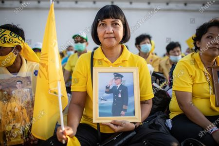 A Thai royalist supporter hold a portrait of Thai King Maha Vajiralongkorn as she gather in front of the Grand Palace at Sanam Luang during a ceremony to celebrate the birthday of late Thai King Bhumibol Adulyadej (Rama 9). Thai King Maha Vajiralongkorn (Rama 10), took part during the ceremony along with other members of the Royal Family.