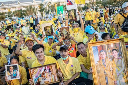 Thai royalist supporters holds portraits of the royal family in front of the Grand Palace at Sanam Luang during a ceremony to celebrate the birthday of late Thai King Bhumibol Adulyadej (Rama 9). Thai King Maha Vajiralongkorn (Rama 10), took part during the ceremony along with other members of the Royal Family.