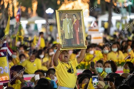 A young Thai royalist shout 'Long Live the  King' while holding a portrait of late Thai King Bhumibol Adulyadej and Queen Sirikit in front of the Grand Palace at Sanam Luang during a ceremony to celebrate the birthday of late Thai King Bhumibol Adulyadej (Rama 9). Thai King Maha Vajiralongkorn (Rama 10), took part during the ceremony along with other members of the Royal Family.