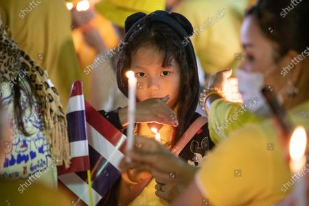 A young Thai royalist supporter light a candle in front of the Grand Palace at Sanam Luang during a ceremony to celebrate the birthday of late Thai King Bhumibol Adulyadej (Rama 9). Thai King Maha Vajiralongkorn (Rama 10), took part during the ceremony along with other members of the Royal Family.