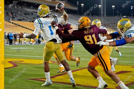 Quarterback Dorian Thompson-Robinson (1) intentionally grounds the football in the end zone for a safety as Arizona State defensive end Michael Matus (91) defends during the second half of an NCAA college football game, in Tempe, Ariz. UCLA won 25-18