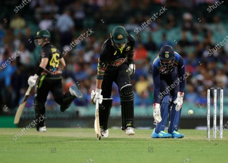 Australia's Moises Henriques, center, makes his ground as India's wicketkeeper KL Rahul, right, retrieves the ball during the second T20 international cricket match between Australia and India at the Sydney Cricket Ground in Sydney, Australia