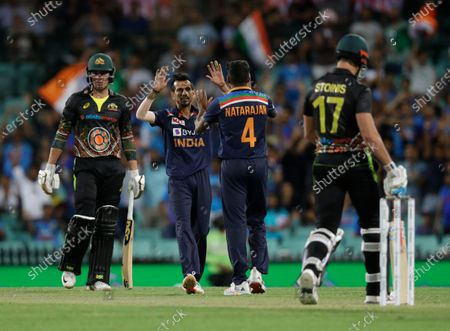 India's T Natarajan, second right, celebrates with teammate Yuzvendra Chahal after dismissing Australia's Moises Henriques, left, during the second T20 international cricket match between Australia and India at the Sydney Cricket Ground in Sydney, Australia