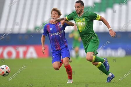 Renato Augusto (R) of Beijing in action against Shuto Abe (L) of Tokyo during the AFC Champions League Round of 16 match between Beijing FC vs FC Tokyo at the Education City Stadium in Al Rayyan, Qatar, 06 December 2020.