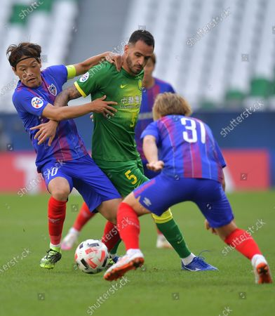 Keigo Higashi (L) of Tokyo in action against Renato Augusto (C) of Beijing during the AFC Champions League Round of 16 match between Beijing FC vs FC Tokyo at the Education City Stadium in Al Rayyan, Qatar, 06 December 2020.