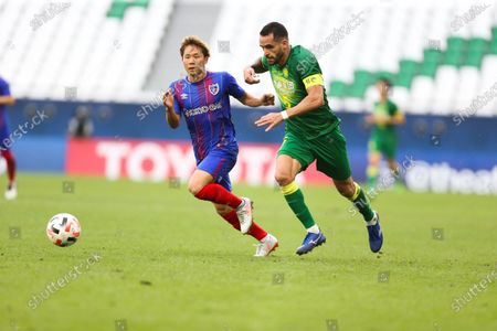 Beijing's Renato Augusto, right and Tokyo's Shuto Abe fight for the ball during a round of 16 AFC Champions League match in Al Rayyan, Qatar