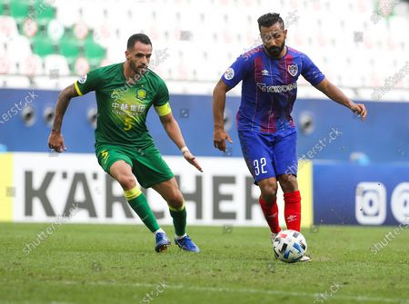 Beijing's Renato Augusto, left, and Tokyo's Joan Oumari fight for the ball during a round of 16 AFC Champions League match in Al Rayyan, Qatar