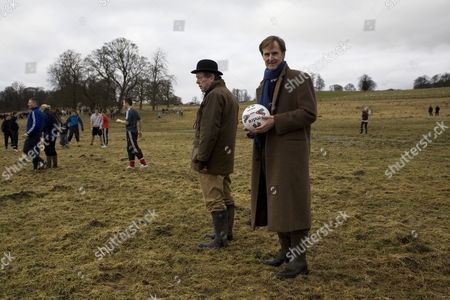 "The Duke of Northumberland, Ralph Percy, holds the football that will be used in Alnwick's traditional Shrovetide Tuesday football match. David Jackson, the match referee, a position known as ""the trumpeter"" stands by the Duke, wearing a bowler hat"