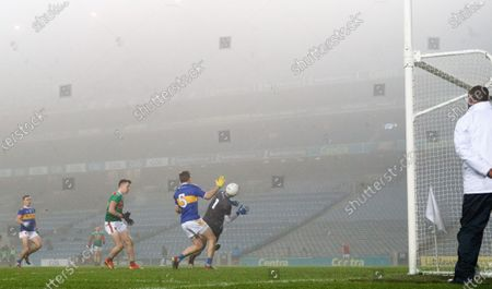 Stock Image of Mayo vs Tipperary. Mayo's Cillian O'Connor scores his sides fifth goal despite Bill Maher and Evan Comerford of Tipperary