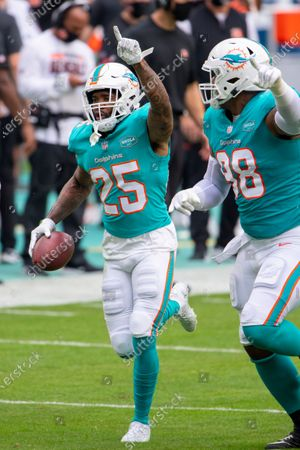 Miami Dolphins cornerback Xavien Howard (25) points to the sky as he celebrates intercepting a pass intended for Cincinnati Bengals wide receiver Tyler Boyd (not shown) along with Miami Dolphins defensive tackle Raekwon Davis (98) during an NFL football game, in Miami Gardens, Fla