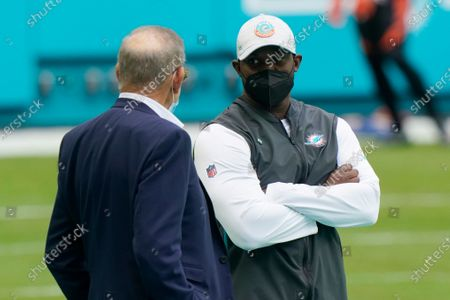 Miami Dolphins owner Stephen Ross speaks to head coach Brian Flores before an NFL football game against the Cincinnati Bengals, in Miami Gardens, Fla