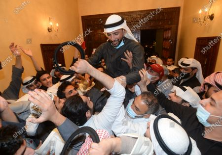 People celebrate after the Kuwait's ex-parliament speaker Marzouq Al-Ghanim (top) wins the parliamentary elections as a MP, in Hawalli Governorate, Kuwait, Dec.6, 2020. The Kuwaiti Emir Sheikh Nawaf Al-Ahmad Al-Jaber Al-Sabah congratulated on Sunday winners in parliamentary elections, the Kuwait News Agency (KUNA) said.    Kuwait on Saturday held parliamentary elections with 326 candidates running for 50 seats. The voting process started from 8 a.m. local time and proceeded until 8 p.m.