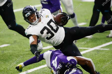 Jacksonville Jaguars running back James Robinson (30) is tackled by Minnesota Vikings safety Anthony Harris (41) during the second half of an NFL football game, in Minneapolis