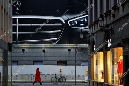Young woman checks her cellphone as she passes a huge advertising board of German car maker Mercedes-Benz in the city center of Munich, Germany