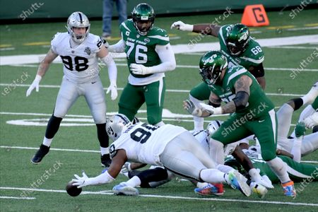 Las Vegas Raiders' Johnathan Hankins (90), bottom center, jumps on a loose ball during the first half an NFL football game against the New York Jets, in East Rutherford, N.J
