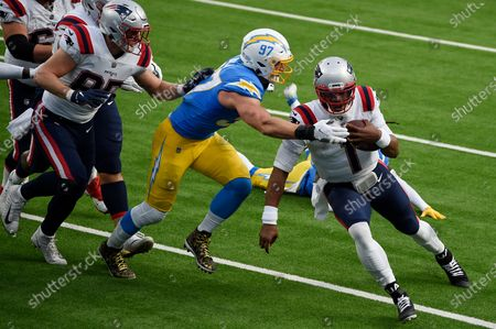 New England Patriots quarterback Cam Newton (1) runs past Los Angeles Chargers defensive end Joey Bosa during the first half of an NFL football game, in Inglewood, Calif