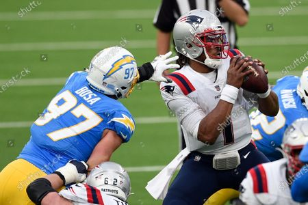 New England Patriots quarterback Cam Newton, right, is pressured by Los Angeles Chargers defensive end Joey Bosa (97) during the first half of an NFL football game, in Inglewood, Calif