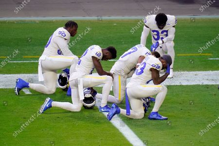Stock Picture of Los Angeles Rams outside linebacker Samson Ebukam (50), wide receiver Van Jefferson (12), wide receiver Robert Woods (17), wide receiver Trishton Jackson (83) and safety Nick Scott (33) kneel during the national anthem prior to an NFL football game against the Arizona Cardinals, in Glendale, Ariz