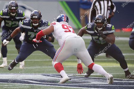Seattle Seahawks offensive tackle Jamarco Jones (73) and offensive guard Damien Lewis (68) square off against New York Giants defensive tackle Dexter Lawrence (97) during the first half of an NFL football game, in Seattle