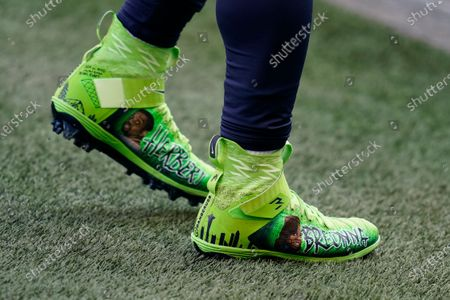 Seattle Seahawks quarterback Russell Wilson wears custom cleats with the name of Bronna Taylor and other victims of police brutality in support of Black Lives Matter as he warms up for an NFL football game against the New York Giants, in Seattle