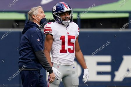 Seattle Seahawks head coach Pete Carroll talks with New York Giants wide receiver Golden Tate (15) before an NFL football game, in Seattle