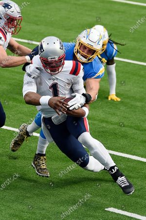 New England Patriots quarterback Cam Newton (1) is tackled by Los Angeles Chargers defensive end Joey Bosa during the first half of an NFL football game, in Inglewood, Calif