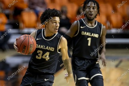Oakland's Jalen Moore and Rashad Williams bring the ball up the court during the first quarter of the NCAA college basketball game against Oklahoma State in Stillwater, Okla