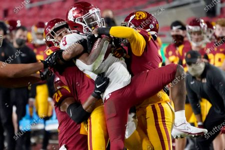 Southern California cornerback Chris Steele, left, and cornerback Olaijah Griffin, right, bring down Washington State wide receiver Renard Bell, center, after a catch during the second half of an NCAA college football game in Los Angeles
